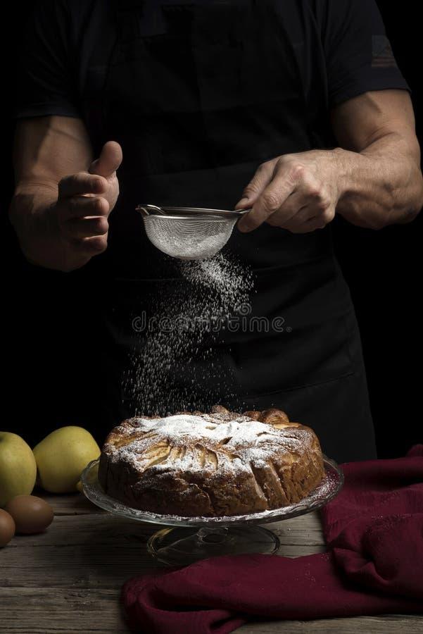 Appeltaart met suikerglazuursuiker op donkere achtergrond en mens in schort stock foto