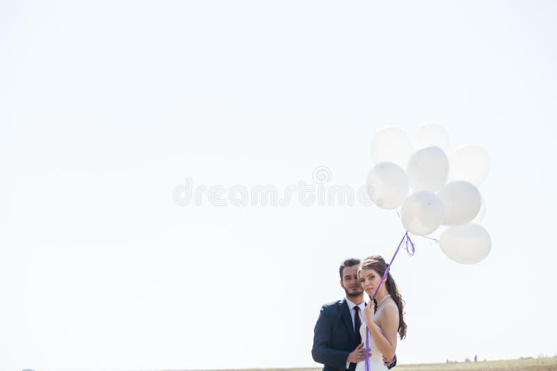 Appena coppia sposata felice con i palloni a disposizione fotografia stock libera da diritti