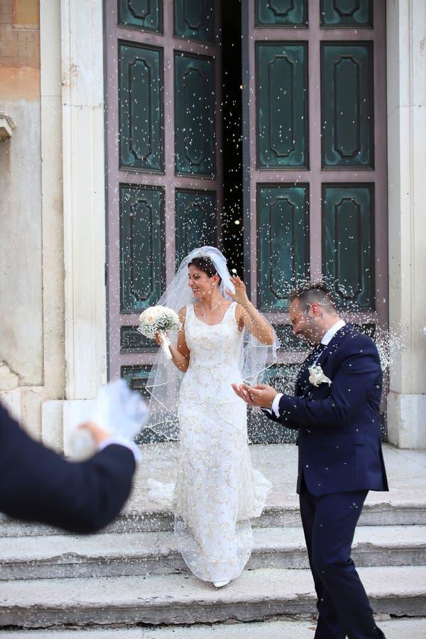Appena coppia sposata felice sotto una pioggia del riso fotografia stock libera da diritti