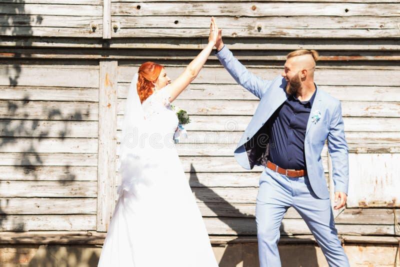 Appena coppie amorose sposate dei pantaloni a vita bassa nella posizione del vestito e del vestito da sposa fotografie stock libere da diritti