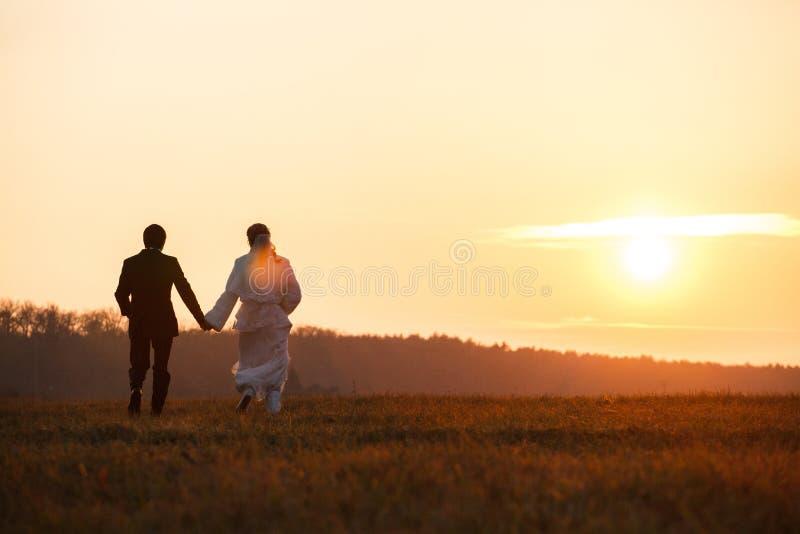 Appena passeggiata della coppia sposata verso un tramonto che tiene il loro Ti delle mani fotografia stock