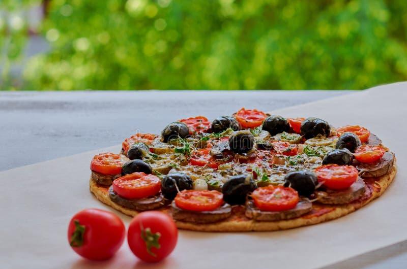 Appena pizza di appoggio della verdura con i funghi, le olive nere e le erbe sul tavolo da cucina grigio decorato con i pomodori  immagine stock