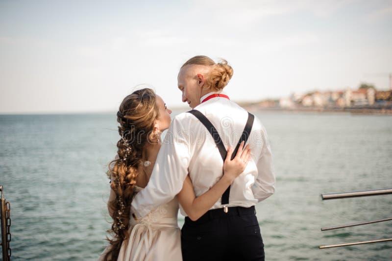 Appena ragazzo sposato e ragazza che si abbracciano sul pilastro sul lago fotografie stock libere da diritti