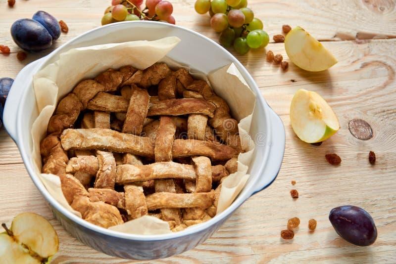 Appena torta di mele americana casalinga cucinata nella forma al forno sulla tavola di legno marrone con l'uva passa e la frutta  fotografia stock