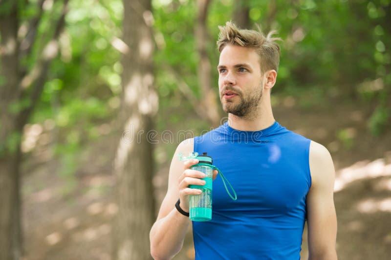 Appena un minuto per riposare l'aspetto atletico dell'uomo tiene la bottiglia con acqua Equipaggi l'atleta nelle cure dei vestiti immagini stock