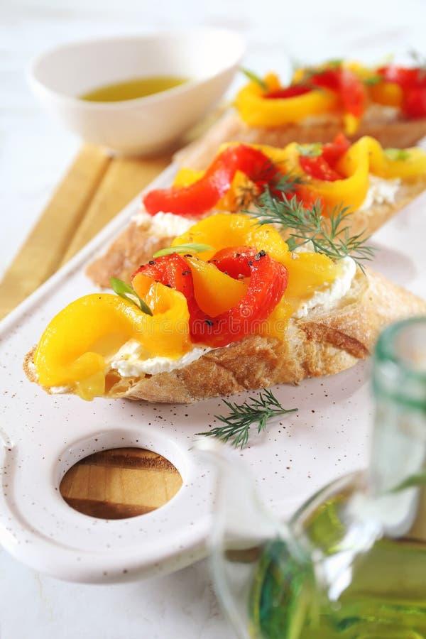 appetisers Skivor av br?d, gr?ddost och grillad spansk peppar med olivolja arkivfoto