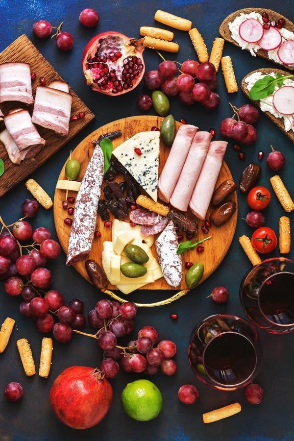 Appetitanregend eine Vielzahl des Aperitif-roten Weins, Frucht, Käse, Wurst auf einem blauen Hintergrund Italienische oder spanis lizenzfreies stockfoto