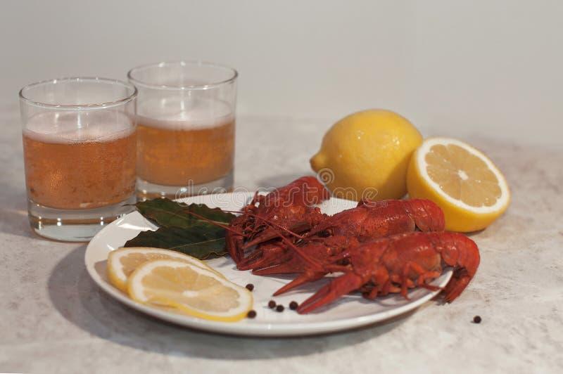 Appetitanregende Platte mit drei roten gekochten Panzerkrebsen, Zitronenscheiben und frischem Bier stockfotografie