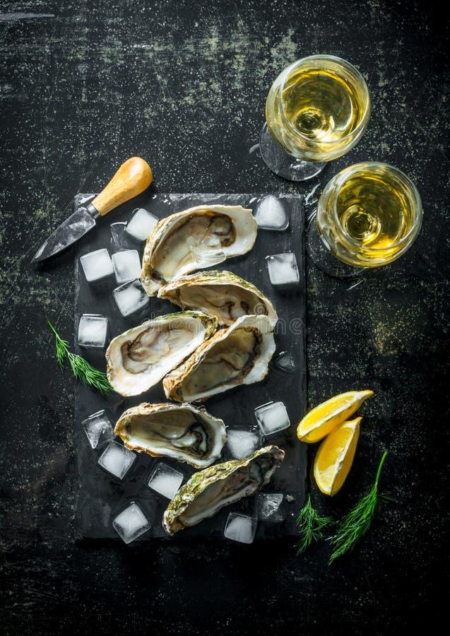 Appetitanregende rohe Austern auf einem Steinbrett mit Eiswürfeln und Gläsern Weißwein stockbild