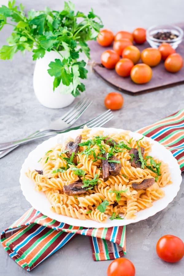 Appetitanregende Teigwaren mit gebratenen Pilzen und frischen Kräutern auf einer Platte lizenzfreie stockbilder