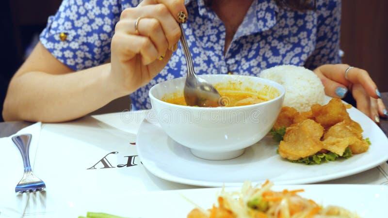 Appetitanregende und geschmackvolle Mahlzeit der Frau im thailändischen Café Reissuppe und Papayasalat stockbilder