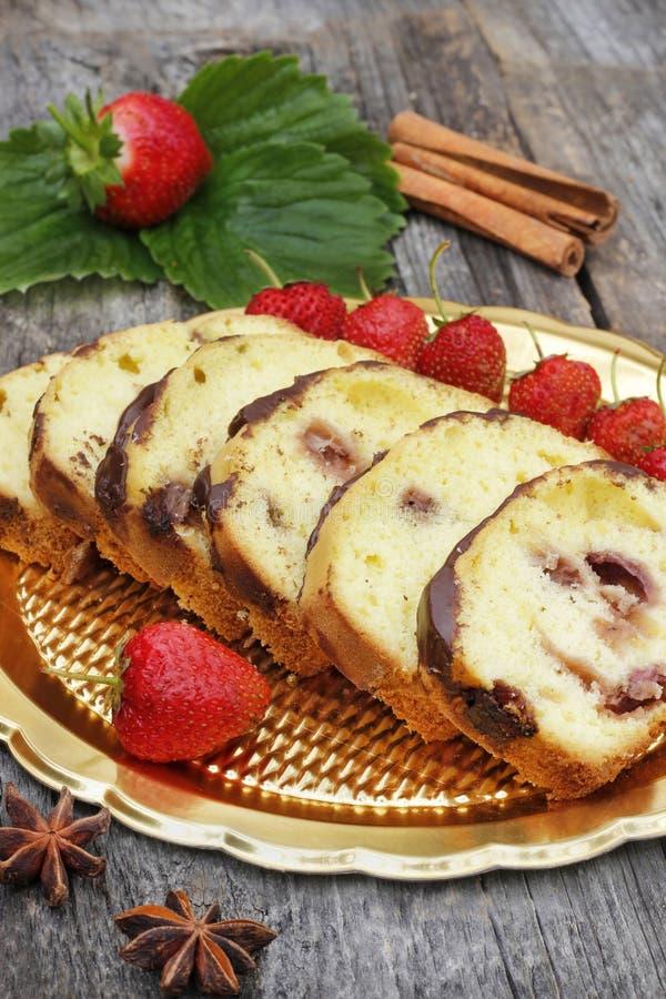 Appetitanregender Bananenkuchen mit Erdbeeren lizenzfreie stockbilder