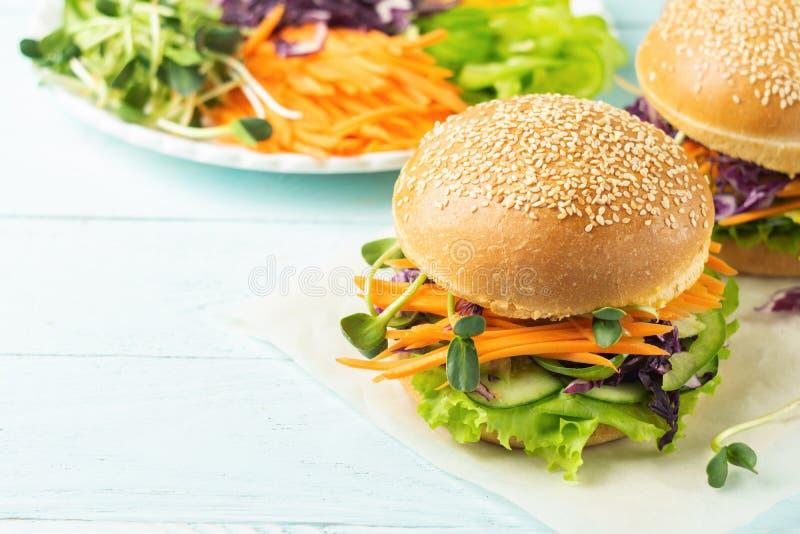 Appetitanregender Burger von den frischen Brötchen des indischen Sesams und von den rohen Gemüse- und jungensprösslingen auf eine stockbild