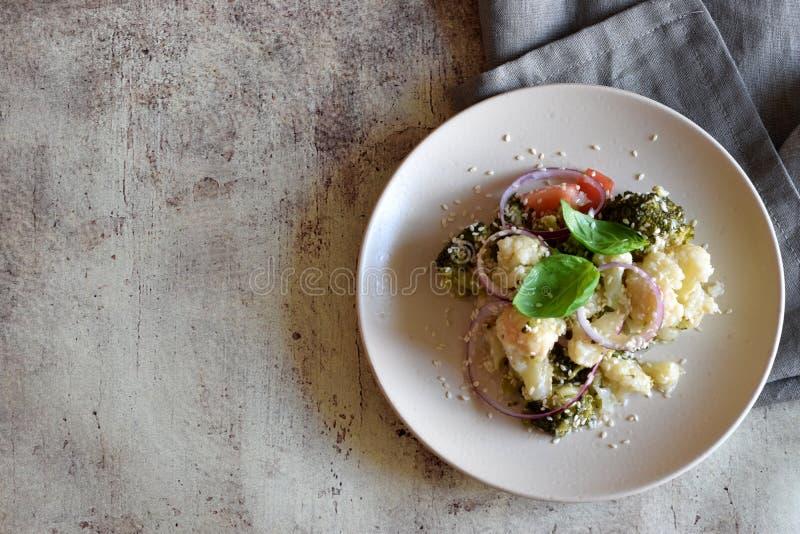 Appetitanregender vegetarischer Gemüsesalat: Brokkoli, Blumenkohl, reife Tomaten, Zwiebeln, indischer Sesam und wohlriechender Ba stockfotografie