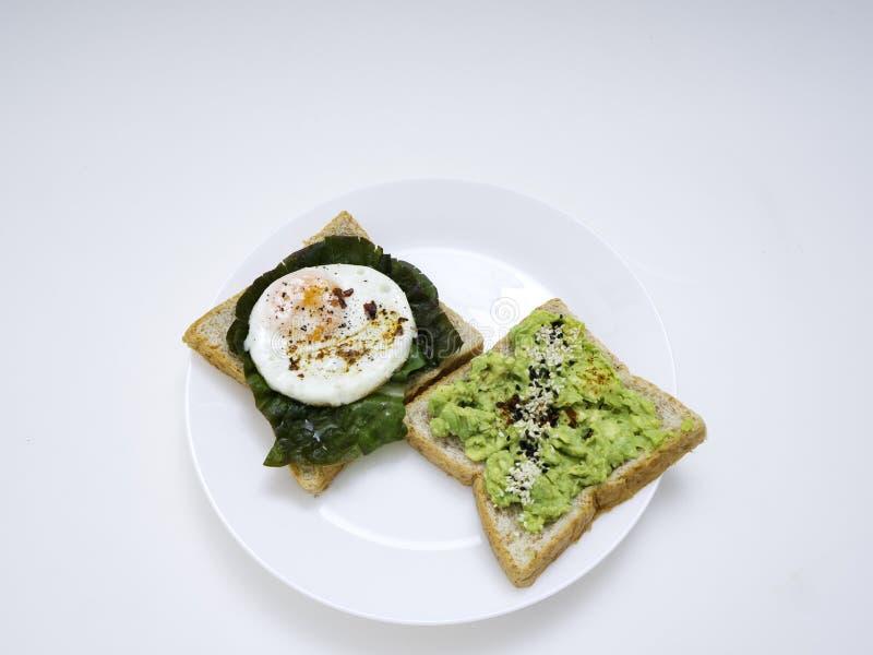 Appetitanregendes bruschetta mit Ei und Avocado auf einer Platte stockfotografie