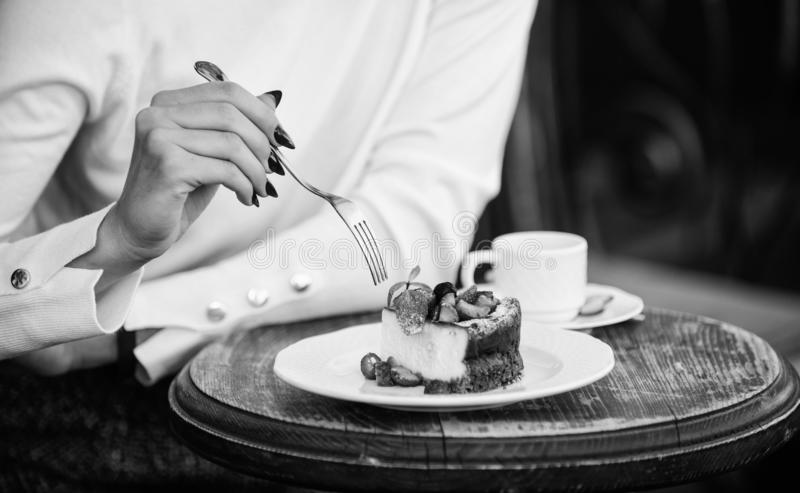 Appetite concept. Dessert cake cup of coffee and female hand with fork close up. Piece of cake with red berry. Gourmet royalty free stock image