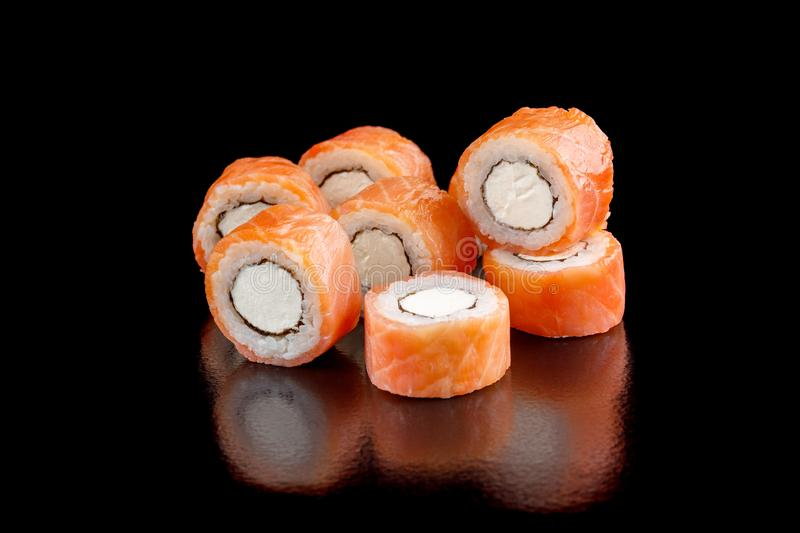 Appetite set of sushi rolls with salmon and Philadelphia cheese on a black background close-up. royalty free stock image