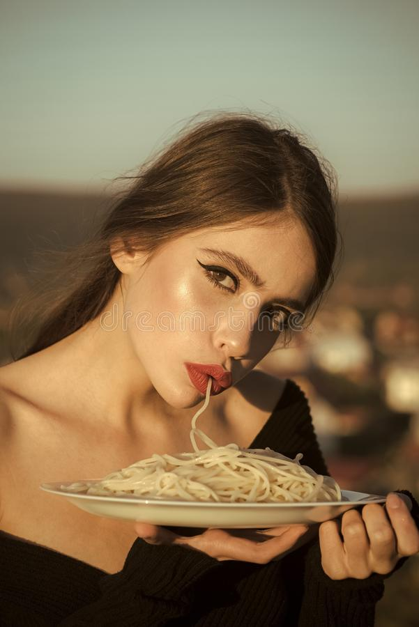 Appetite of young woman with macaroni. appetite and hunger of woman with red lips. royalty free stock photos