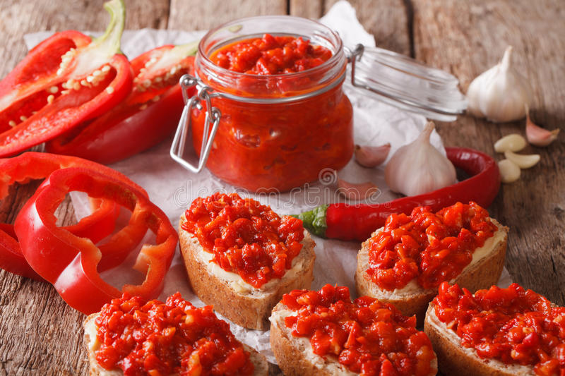 Appetizer ajvar from peppers with garlic close-up. horizontal. Appetizer ajvar from peppers with garlic close-up on the table. horizontal stock image