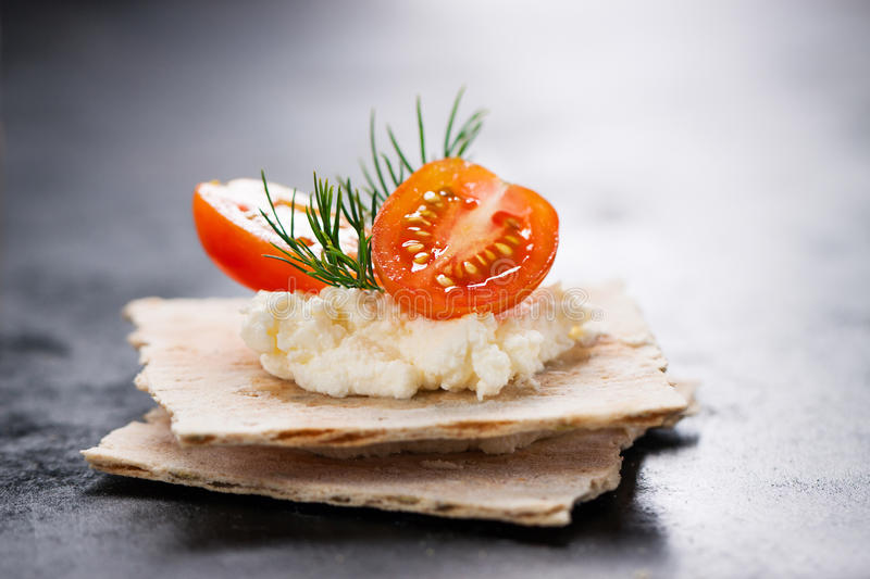 Appetizer canape with cherry tomato, cheese and dill on a small loaf of bread. Closeup royalty free stock photography