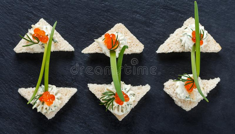 Appetizer canape with red caviar and cream cheese on stone slate background close up. stock photo