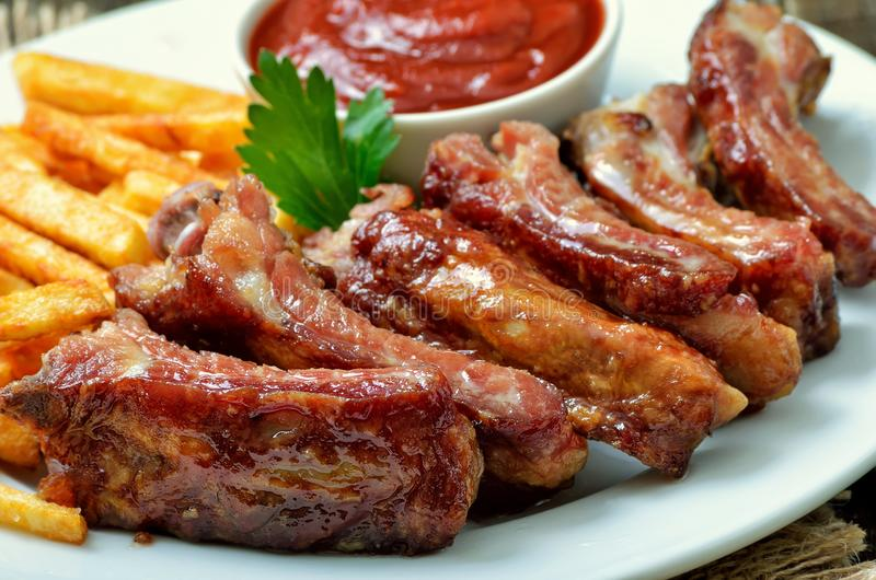 Appetizer fried pork ribs. On white plate, close up view stock image