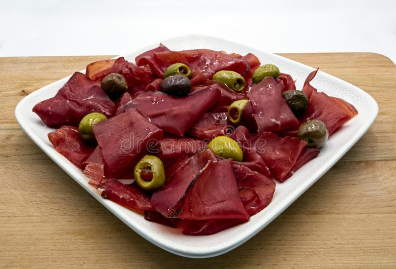 Appetizer of italian bresaola and olives on white plate. Wooden table, white background stock images