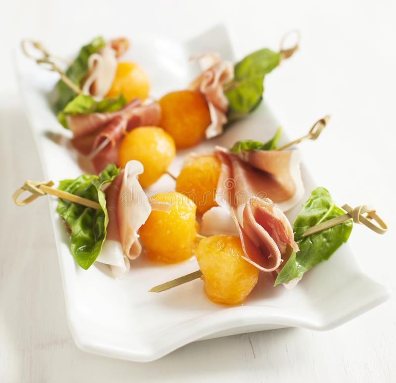 Appetizer with melon and prosciutto on skewers royalty free stock photo