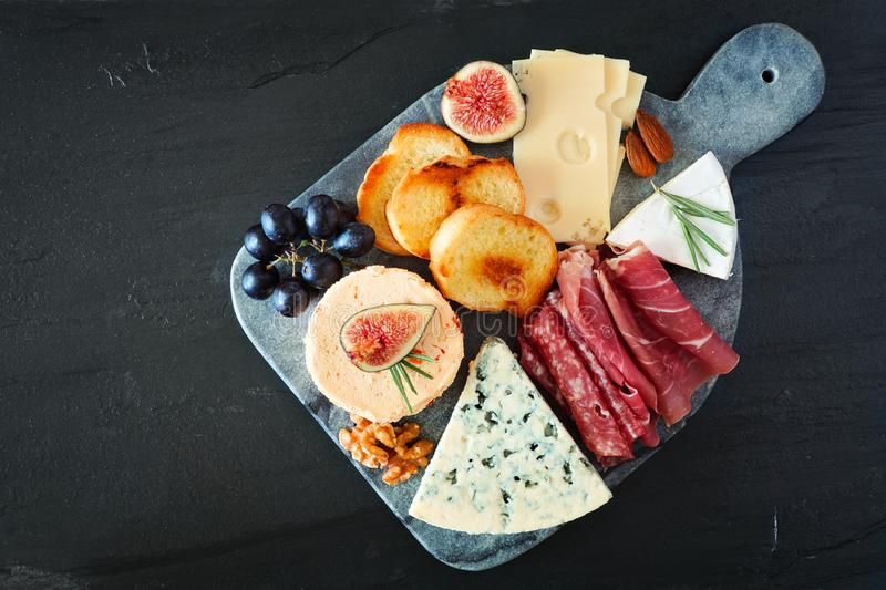 Appetizer platter with assorted cheeses and meats, overhead view on a dark stone background stock images