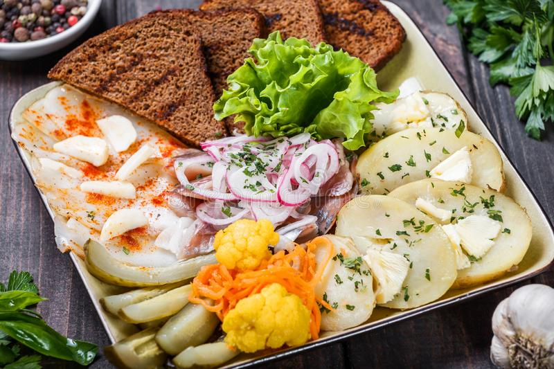 Appetizer platter, baked potato, delicious sliced pork fat with spices, sliced smoked fish with onions, pickles and bread stock images