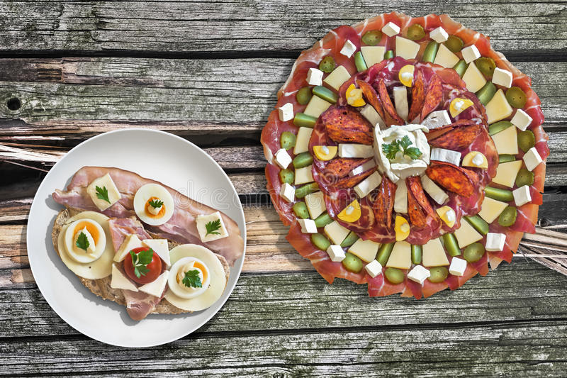 Appetizer Savory Dish With Bacon Cheese Egg Gammon And Tomato Sandwich Set On Old Wooden Picnic Table. Traditional, garnished, Appetizer Savory Dish Meze, with royalty free stock images