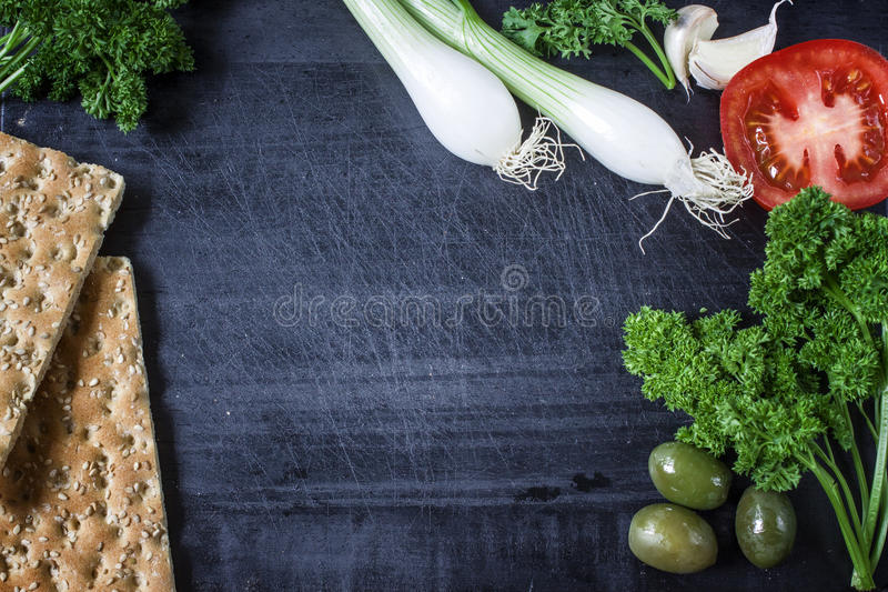 Appetizer set on wooden board. With olives,parsley,garlic. Top view. Dark background. royalty free stock photo