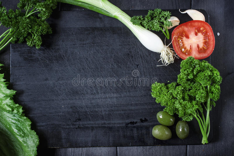 Appetizer set on wooden board. With olives,parsley,garlic. Top view. Dark background. royalty free stock image