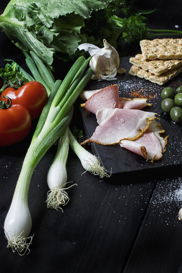 Appetizer set on wooden board. With olives,parsley,tomato,garlic. Top view. Dark background. stock images
