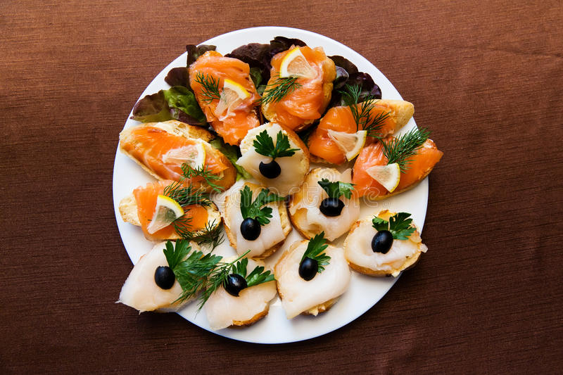 Appetizer sliced fish on a platter on the table in the restaurant stock photo