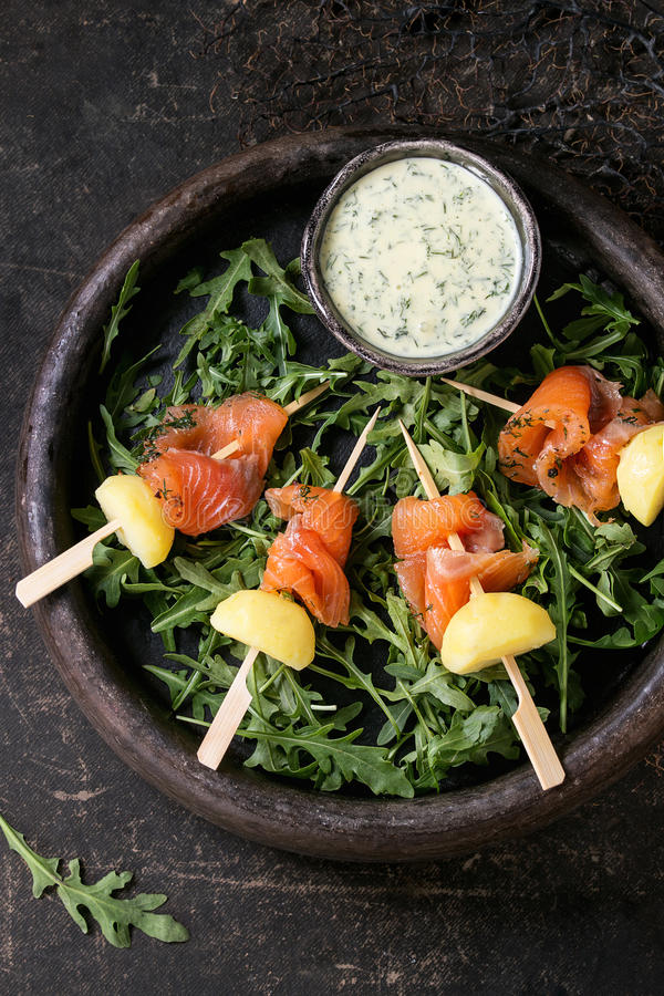 Appetizer with smoked salmon and potatoes. Delicious Appetizer with smoked salted salmon and boiled potatoes on skewers served with creamy dill sauce and arugula stock photos