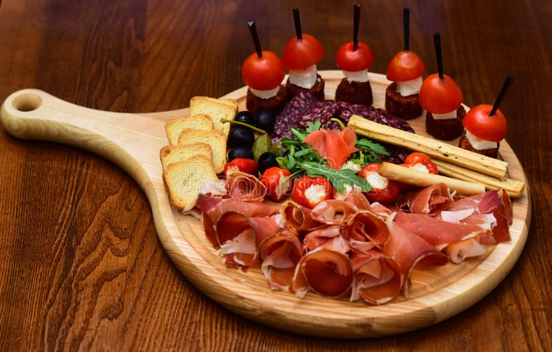 Appetizer table with italian antipasto snacks. Cold meat cuts and canape with tomatoes served on appetizer platter. The. Taste from space royalty free stock photos