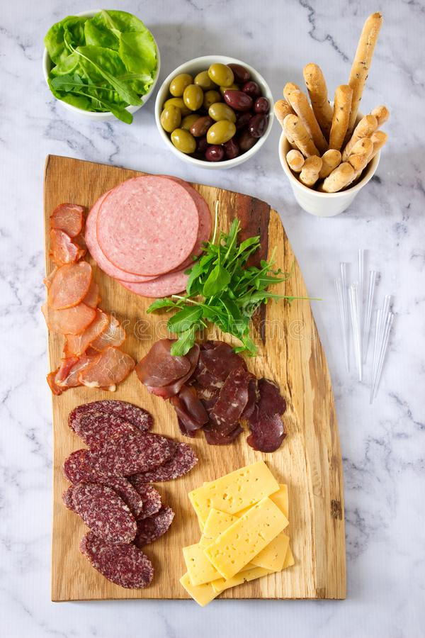 Appetizer table for wine or beer with sausages, dried meat and cheese, served with grissini, herbs and olives. stock photography