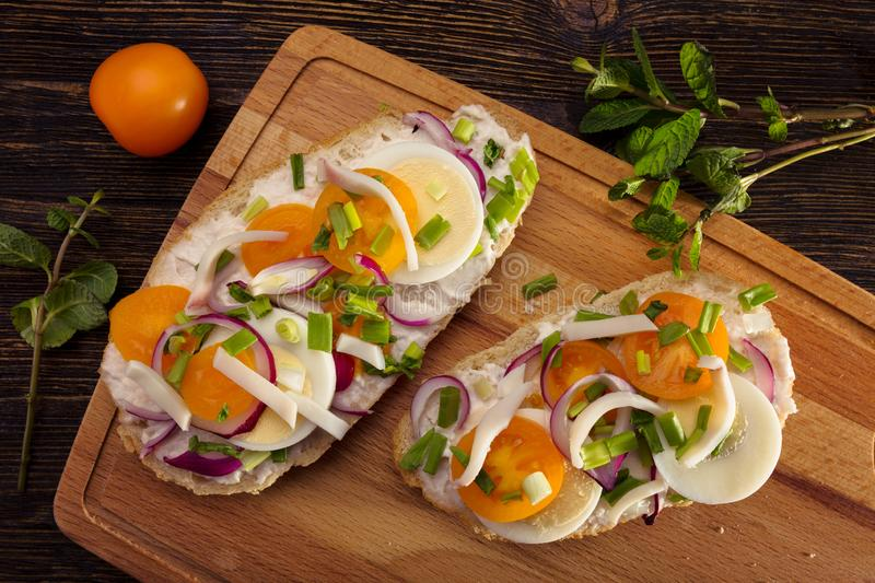 Appetizer toasts with pieces of squid, yellow tomatoes, sliced eggs and red onion, shrimp paste royalty free stock photo