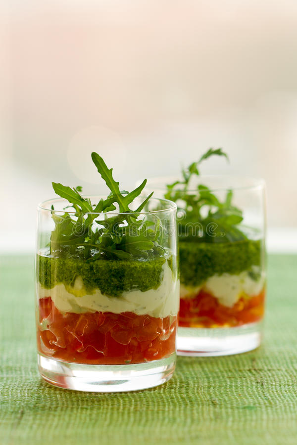 Appetizer with tomato,cheese and pesto. In glasses royalty free stock photography