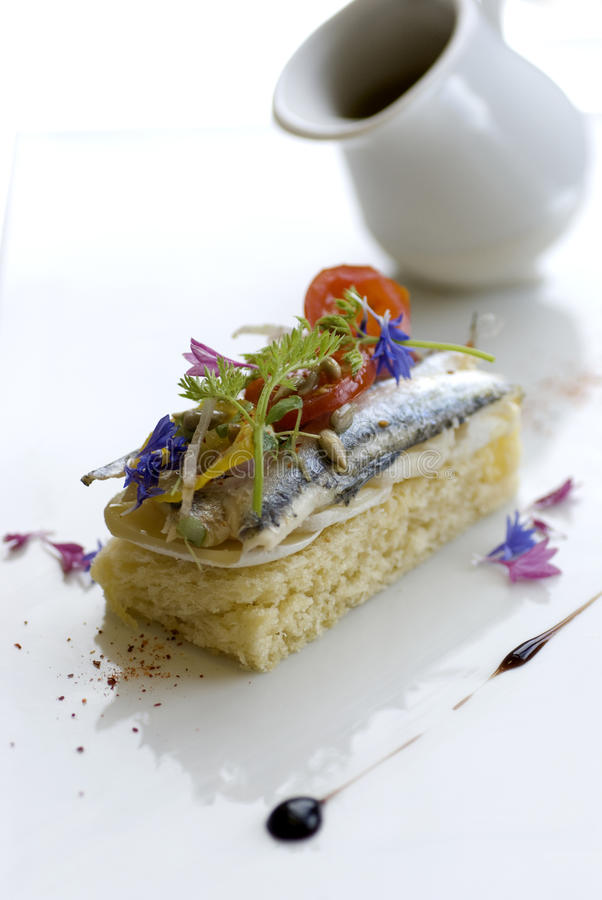Appetizers. With sardines and tomato in a restaurant royalty free stock photo