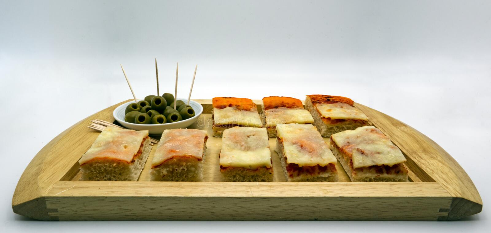 Appetizers with antipasti snacks. Pizza and olives green without stones on wooden tray, white background royalty free stock photos