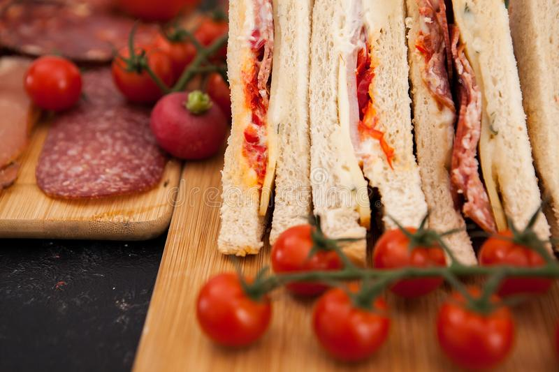 Appetizers and club sandwiches. On wooden boards royalty free stock photography