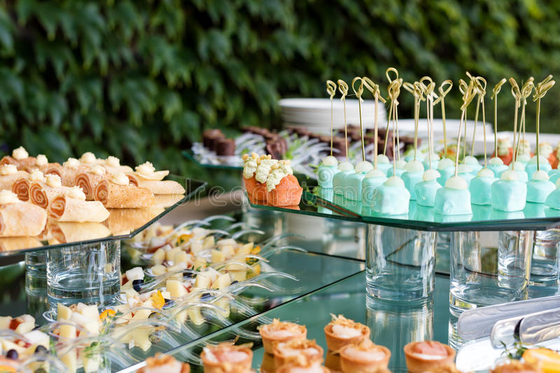 Appetizers, finger food, party food, sliders. Canape, tapas. Served table at summer terrace cafe. Catering service. Outdoor restaurant table with food royalty free stock photos