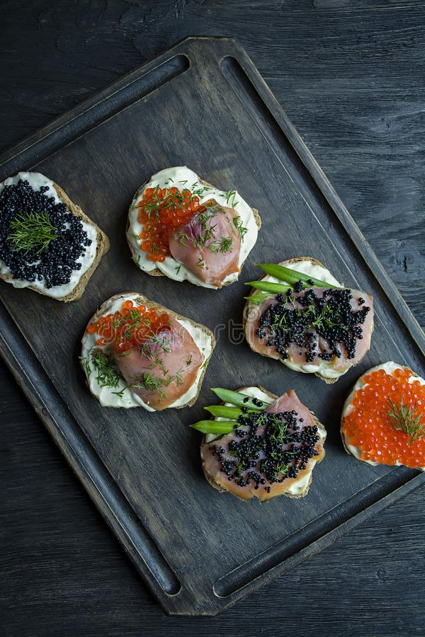 Appetizers with red caviar and black caviar on a dark chopping board. Close-up. Dark wooden background royalty free stock photo