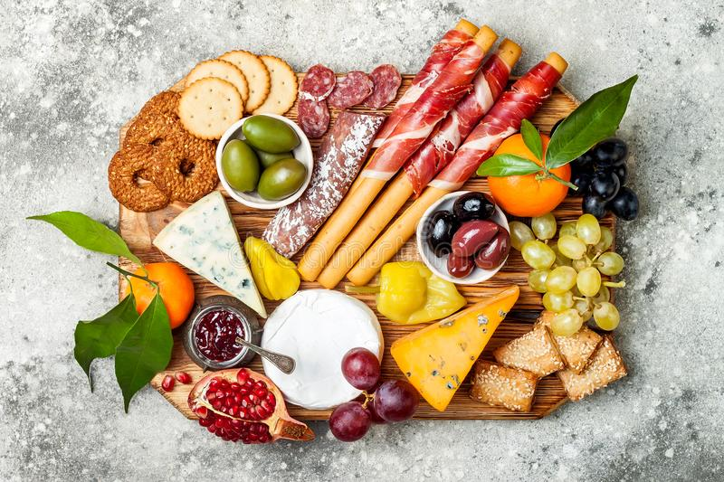 Appetizers table with antipasti snacks. Cheese and meat variety board over grey concrete background. Top view, flat lay. stock images