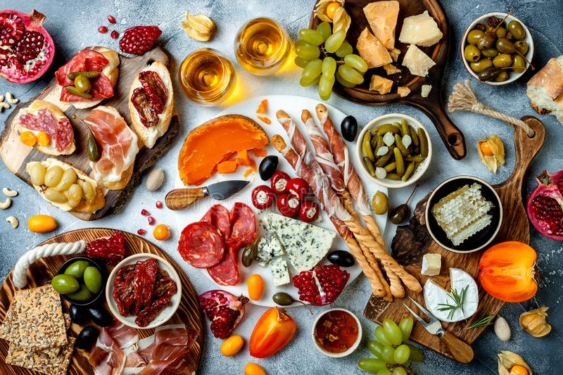 Appetizers table with antipasti snacks and wine in glasses. Bruschetta or authentic traditional spanish tapas set, cheese and meat. Platter over grey concrete stock image