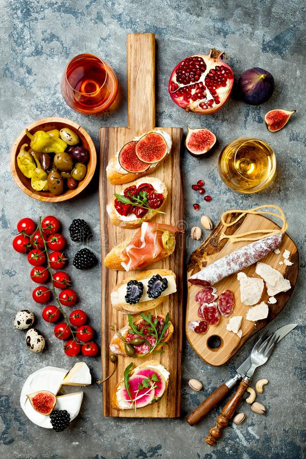 Appetizers table with italian antipasti snacks and wine in glasses. Brushetta or authentic traditional spanish tapas set. Cheese variety board over grey royalty free stock image