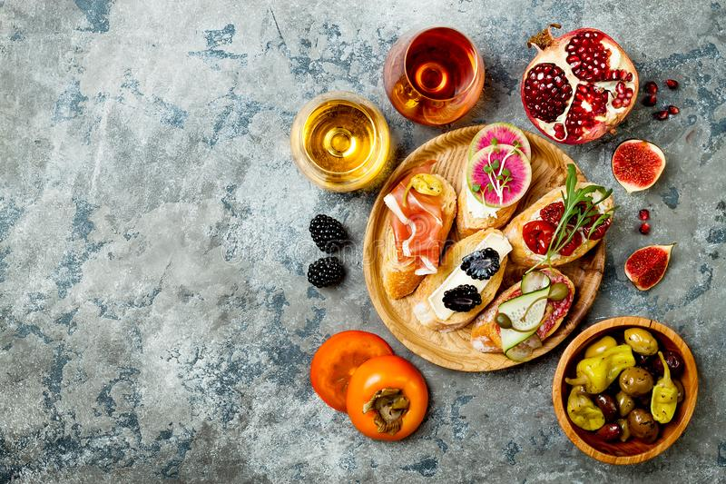 Appetizers table with italian antipasti snacks and wine in glasses. Brushetta or authentic traditional spanish tapas set stock photography