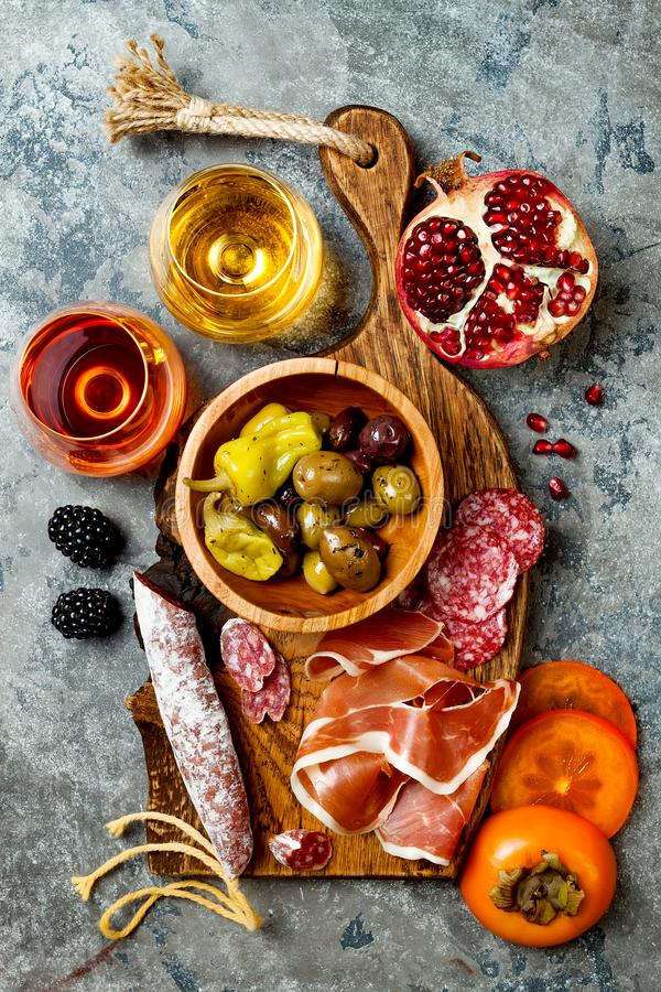 Appetizers table with italian antipasti snacks and wine in glasses. Charcuterie board over grey concrete background. Top view stock images